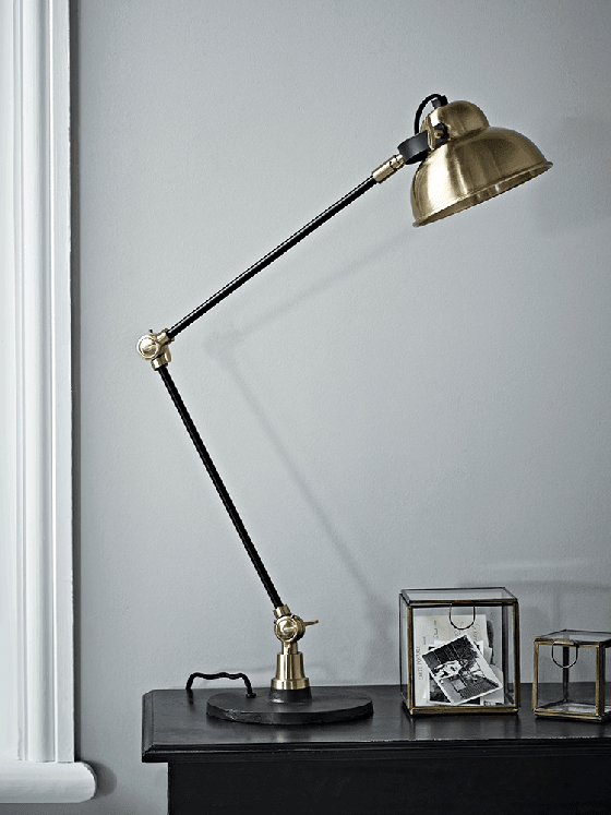Brass and black desk lamp by Cox and Cox against pale grey wall