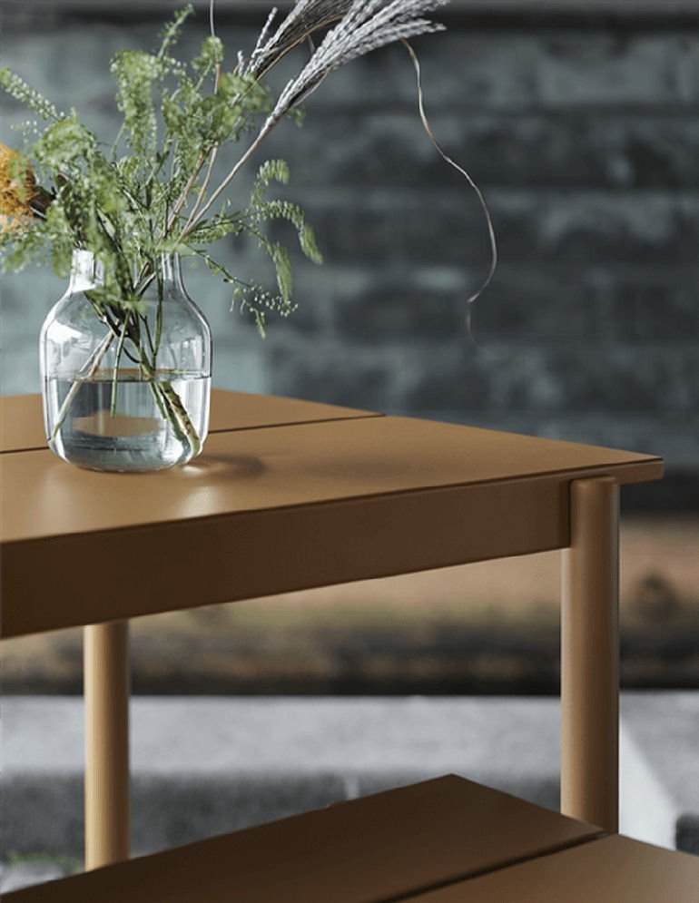 Close up of the Linear Outdoor Table by Muuto with clear vase of wild flowers