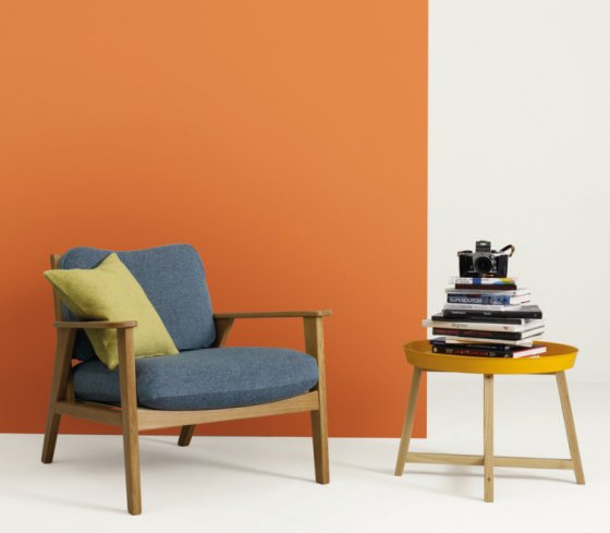 Louis armchair with grey cushions and yellow scatter cushion against orange background with yellow side table