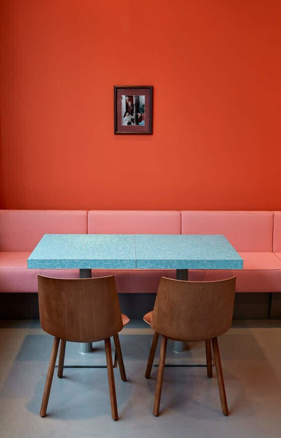 Orange wall, pink banquette and turquoise table in Louis Pretty deli in Berlin