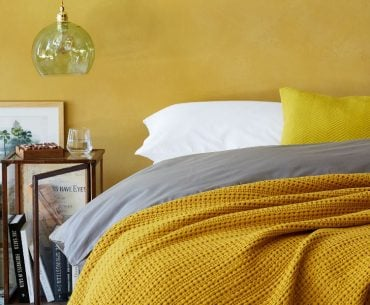 yellow cotton throw and grey bedding